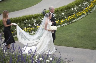 bride-and-father-walk-down-path-next-to-green-lawn