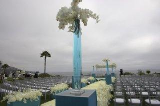 vase-filled-with-blue-water-and-white-flowers-sits-on-top-of-a-blue-box-at-end-of-aisle