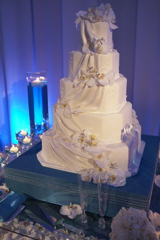white-cake-decorated-with-fondant-ribbons-and-white-orchids