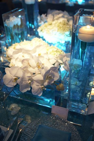 orchids-and-floating-candle-in-glass-square-vases-with-blue-lighting
