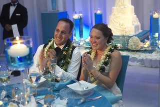 newlyweds-wear-flower-leis-while-seated-at-table