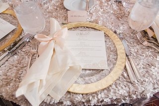 wedding-reception-with-textured-linen-flower-gold-charger-plate-white-napkin-with-light-pink-bow