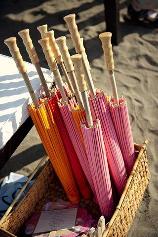 pink-and-orange-parasols-in-basket-at-ceremony