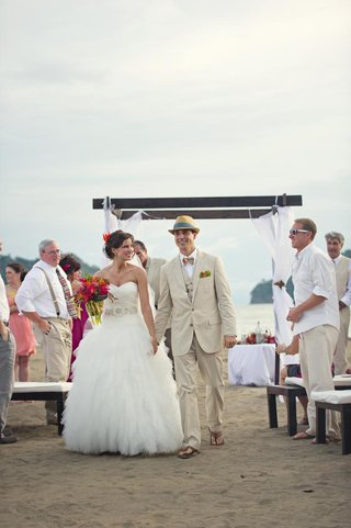 bride-and-groom-walk-up-aisle-in-flip-flops-in-sand