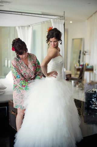 woman-in-printed-robe-helps-bride-into-wedding-dress