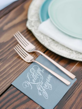 personalized-blue-napkins-with-calligraphy-of-couples-names-with-silverware-on-a-wooden-table