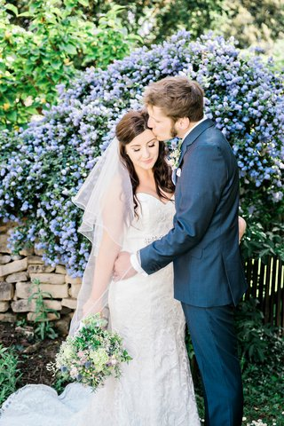 groom-kissing-bride-forehead-garden-english-british-england-wedding-wildflower-bouquet-blue-suit
