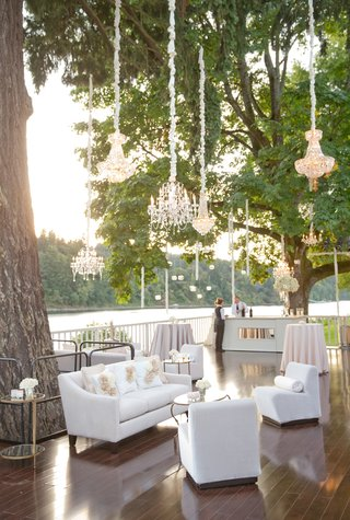 river-porch-wedding-lounge-with-couches-and-chandeliers-in-tree