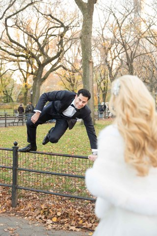 a-groom-in-a-black-tuxedo-jumps-a-fence-in-new-yorks-central-park-to-get-to-bride
