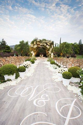 wedding-ceremony-outdoor-grey-wash-wood-aisle-runner-white-initials-monogram-green-boxwood-hedge