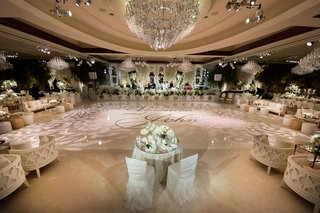 sweetheart-table-in-front-of-large-white-dance-floor-lighting-projections-names-on-dance-floor