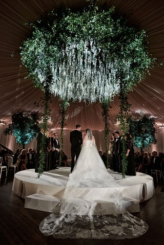 bride-in-strapless-wedding-dress-and-cathedral-veil-on-raised-round-stage-ceremony-wedding-greenery