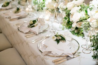 wedding-reception-place-setting-white-linens-silver-charger-plate-fresh-flower-calla-lily-leaves