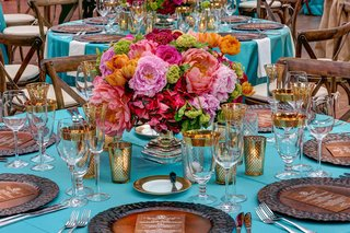 wedding-reception-centerpiece-with-pink-orange-and-green-flowers-on-turquoise-tablecloth