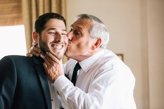 father-of-the-groom-kisses-his-sons-cheek