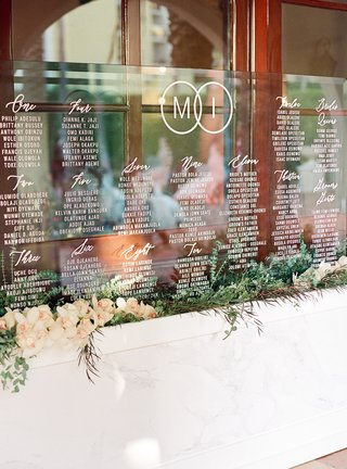 acrylic-sheet-with-wedding-seating-chart-in-bed-of-orchids-and-greenery