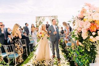 bride-in-custom-trish-peng-wedding-dress-groom-walking-up-aisle-yellow-flower-petals-blue-chairs
