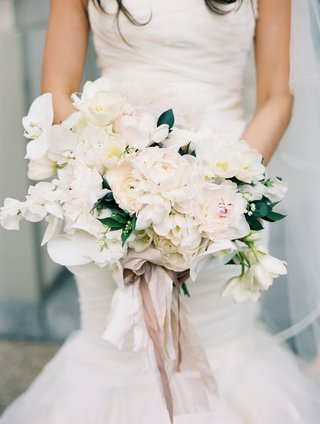 light-white-bright-bouquet-with-flowers-tied-with-ribbon-held-by-bride-in-mermaid-wedding-dress
