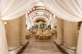 wedding-reception-gold-chairs-tall-centerpieces-greenery-white-flowers-columns-white-drapery-drapes