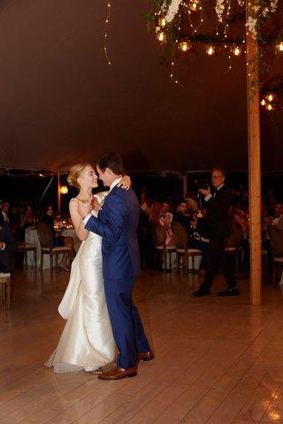bride-in-classic-wedding-dress-groom-in-blue-suit-dancing-on-wood-floor-to-first-dance-song