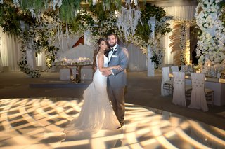 bride-in-form-fitting-wedding-dress-groom-in-grey-tuxedo-dance-floor-with-woven-light-projection