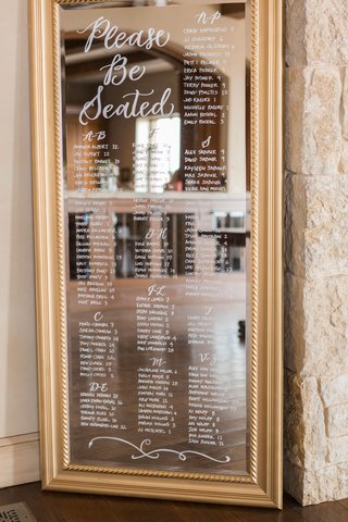 wedding-reception-please-be-seated-calligraphy-seating-chart-gold-frame-white-lettering-by-last-name