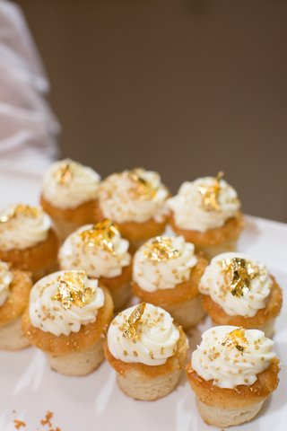 cupcakes-with-white-frosting-and-gold-sprinkles-at-wedding
