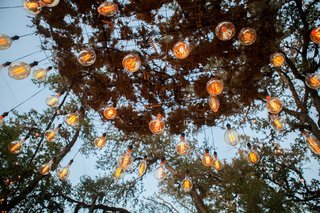 wedding-reception-outdoors-trees-with-light-bulbs-hanging-edison-vintage
