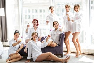 bride-and-bridesmaids-toast-drinks-with-flower-garnishes-in-bridal-suite-high-rise