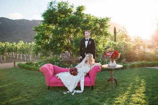 bride-in-jim-hjelm-wedding-dress-and-groom-relax-on-pink-couch-at-california-vineyard