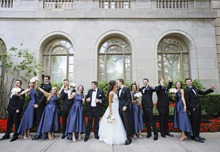 bride-in-hayley-paige-kisses-groom-in-tuxedo-bridesmaids-in-alfred-sung-high-low-satin-navy-dresses