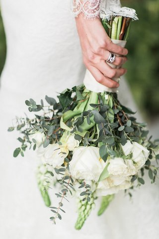 bride-holds-bouquet-of-white-roses-greenery-and-wears-diamond-wedding-bands-and-engagment-ring