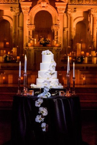 four-layer-wedding-cake-on-black-table-candlesticks-orchids-cascading-down-front