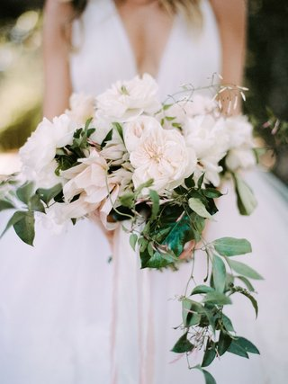 bride-in-v-neck-wedding-dress-neutral-wedding-bouquet-greenery-trailing-vine-fluffy-flowers-roses