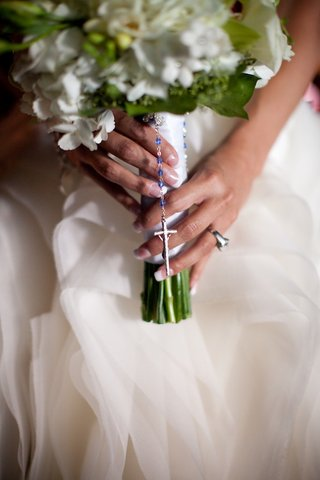 bride-holds-white-and-green-bouquet-with-blue-bead-rosary