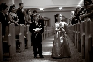 black-and-white-photo-of-flower-girl-handing-flowers-to-guests