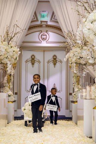 shannon-perkins-and-tahir-whitehead-kids-wagon-cute-signs-around-necks-white-gold-ballroom-decor