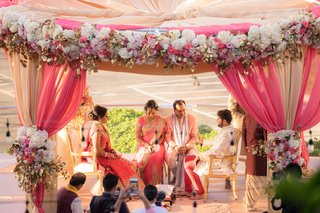 indian-wedding-outdoor-ceremony-circular-mandap-pink-gold-white-flowers-peach-sunset-colors-gold