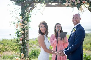 bride-and-groom-under-wood-chuppah-flowers-greenery-sister-in-law-officiant-pink-dress-lace-halter