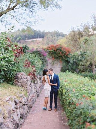bride-in-short-knee-length-wedding-dress-light-blue-heels-and-open-back-with-groom-in-navy-suit