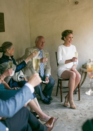 bride-in-a-short-mod-dress-with-long-sleeves-tan-jimmy-choo-heels-laughs-with-guests