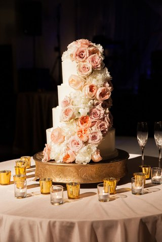 a-four-tier-white-wedding-cake-with-cascading-ivory-and-blush-flowers
