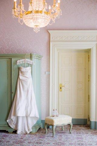 wedding-dress-hanging-in-vintage-villa-room