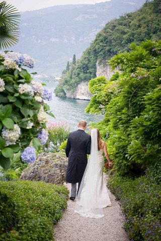 bride-and-groom-walking-through-gardens-in-lake-como