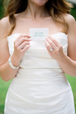 bride-holding-white-escort-card-with-turquoise-calligraphy