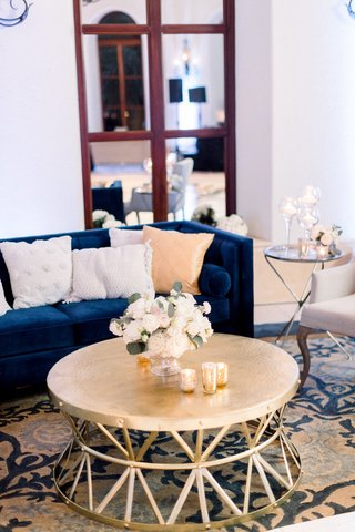 wedding-reception-ballroom-navy-blue-velvet-tufted-sofa-white-pom-tassel-pillows-gold-coffee-table