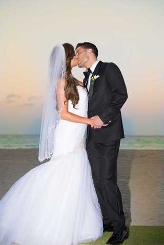 acqualina-resort-spa-wedding-couple-bride-in-veil-mermaid-dress-groom-in-tuxedo-kiss-on-beach