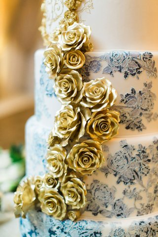 wedding-cake-with-blue-and-white-ombre-flower-design-and-gold-sugar-flowers-down-side