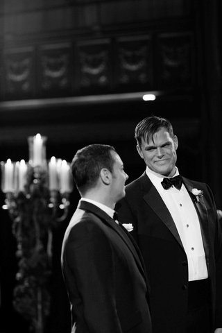 black-and-white-photo-of-matthew-christopher-in-a-tuxedo-with-his-groom-at-ceremony