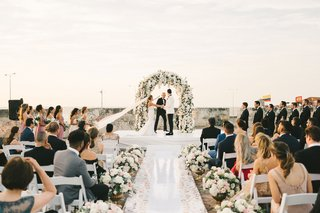 wedding-ceremony-flower-wall-white-shiny-aisle-runner-low-flowers-in-gold-urns-colombia-outdoor